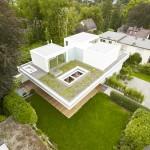 บ้านสามชั้นแบบโมเดิร์น สีขาวดูเรียบหรู พร้อมสนามหญ้าและแปลงดอกไม้ลอยฟ้า