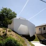 บ้านแนวโมเดิร์นสีขาวรูปทรงแปลกตา มีผนังเป็นผืนผ้าโอบล้อมตัวบ้านไว้อีกชั้น