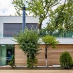 บ้านเดี่ยวสองชั้นแบบโมเดิร์น พร้อมพื้นที่สีเขียวรอบบ้าน และต้นไม้ใหญ่อยู่ตรงกลาง