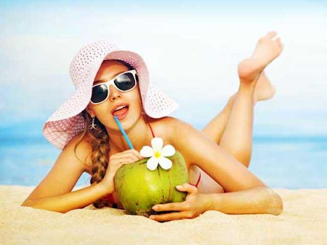 woman-beach-drinking-coconut