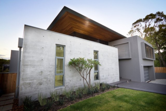 Comely-contemporary-home-design-in-australia-featuring-exterior-concrete-wall-idea-with-green-grass-lawn-and-garden-945x630