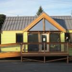 บ้านคอนเทจสีเหลือง มาพร้อมเฉลียงหน้าบ้าน และทางลาดสำหรับผู้สูงอายุ