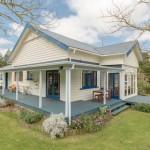 บ้านไม้สไตล์คันทรีโทนสีขาว – น้ำเงิน กลางพื้นที่ธรรมชาติ มาพร้อมเฉลียงโปร่งรอบบ้าน