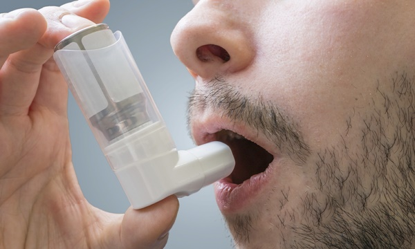 Asthmatic man suffers from asthma and is using inhaler.