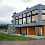 บ้านสองชั้นรูปทรงสมัยใหม่ ตกแต่งด้วยกระจกและงานเหล็ก ท่ามกลางสวยสวน