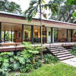 บ้านตากอากาศยกพื้นสูง รูปทรงหน้ากว้าง ตกแต่งอย่างโปร่งโล่งด้วยหน้าต่างไม้