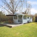 บ้านเดี่ยวขนาดเล็ก สไตล์คอเทจ มาพร้อมเฉลียงหน้าบ้าน และสนามหญ้าโล่งกว้าง