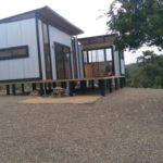 บ้านสวนสไตล์โมเดิร์น ออกแบบด้วยเมทัลชีท 1 ห้องนอนขนาดเล็กๆ บิวท์อินภายในด้วยงานไม้ มาพร้อมเฉลียงหน้าบ้าน