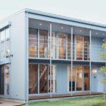 บ้านโมเดิร์นรูปทรงกล่องสี่เหลี่ยม โทนสีเทา ตกแต่งด้วยกระจก ภายในมินิมอลงานไม้