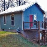 บ้านกระท่อมหลังเล็ก โทนสีฟ้าพาสเทล 1 ห้องนอนบนชั้นลอย 1 ห้องน้ำในตัว ตกแต่งโดยรอบด้วยพรรณไม้แบบสวนป่า