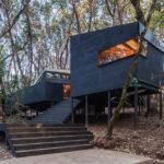 บ้านตากอากาศ ตกแต่งด้วยงานไม้สีดำเข้ม ยกพื้นพองาม เปิดโล่งรับธรรมชาติ พร้อมการตกแต่งภายในแบบมินิมอล สบายตา