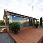 บ้านกระท่อมสมัยใหม่ ดีไซน์หลังเล็กๆ ผสมงานไม้เข้ากับกระจก พร้อมเฉลียงบ้านขนาดใหญ่