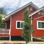 แบบบ้านชั้นเดียวยกพื้นต่ำ แต่งผนังไม้แดง มาพร้อมระเบียงนั่งเล่นรับลม เหมาะสร้างเป็นบ้านสวน
