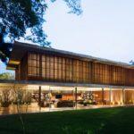 บ้านสองชั้นสไตล์โมเดิร์น ออกแบบชั้นล่างโปร่งโล่งด้วยผนังกระจก และสร้างความโดดเด่นให้ชั้นบนด้วยผนังไม้