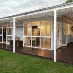บ้านชั้นเดียวสไตล์คอจเทจ โดดเด่นด้วยผนังและระแนงไม้สีขาว พร้อมพื้นที่พักผ่อนเฉลียงติดสวน