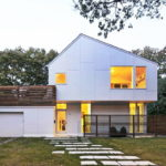 บ้านสองชั้นสไตล์โมเดิร์น ตกแต่งผนังภายนอกในโทนสีขาว ให้บรรยากาศที่เรียบง่ายและสงบเงียบ