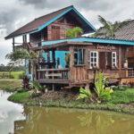 บ้านไร่กลางทุ่ง สร้างขึ้นจากไม้เก่าทั้งหลัง แวดล้อมด้วยท้องทุ่งเขียวขจี และหนองน้ำเย็นใส